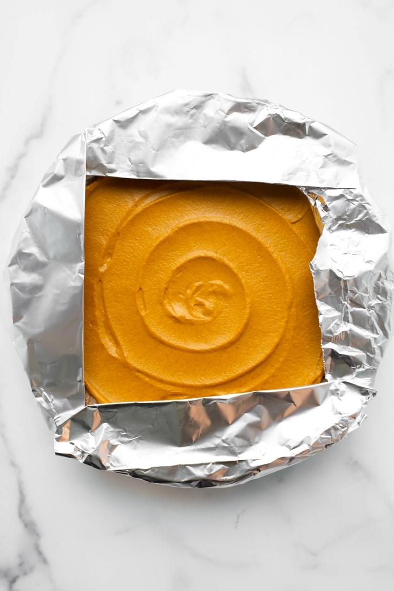 prebaked vegan pumpkin pie with foil strips on crust