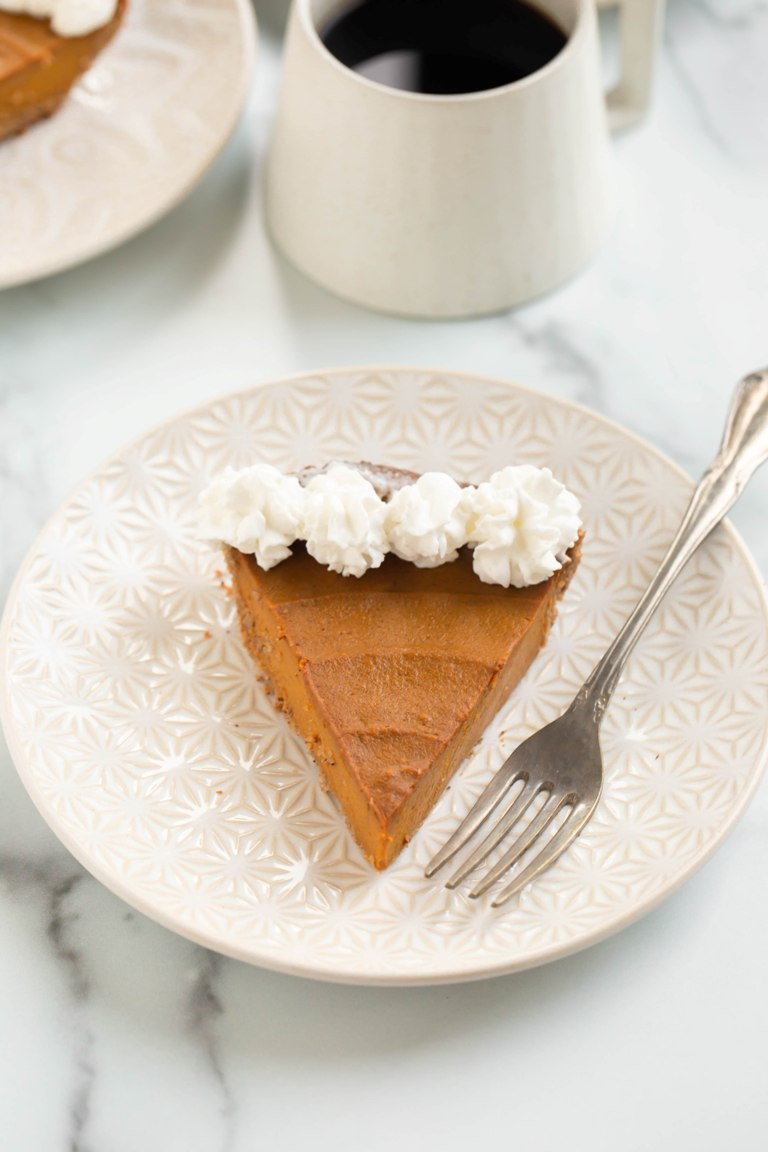 slice of vegan pumpkin pie on round plate with cup of coffee