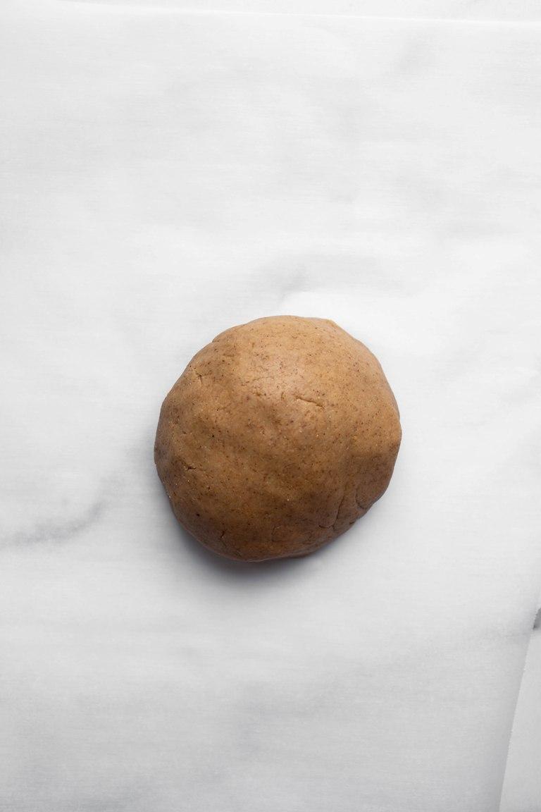ball of vegan gluten-free pie dough on white marble