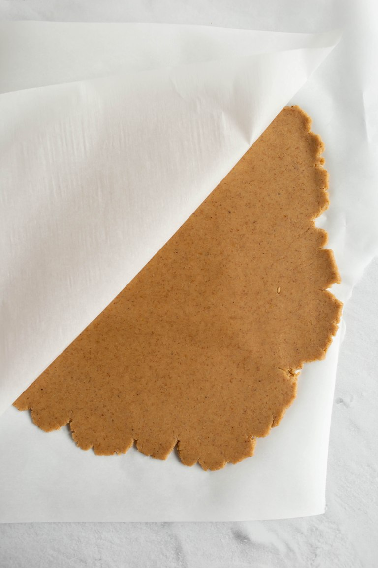 rolled out pie dough between 2 pieces of parchment paper