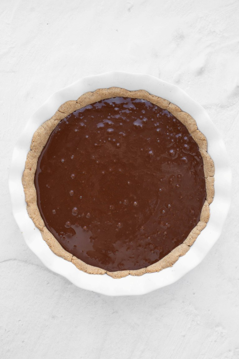 melted chocolate pie filling on top of prebaked crust