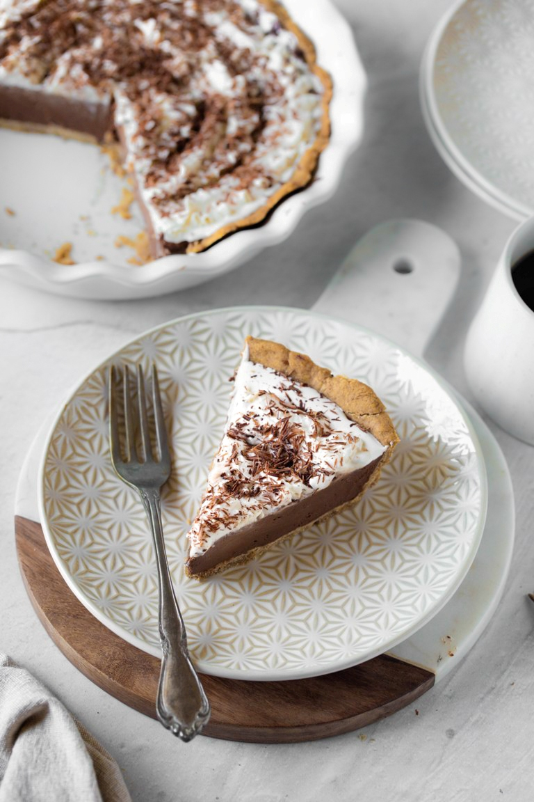 slice of chocolate cream pie on white plate with fork