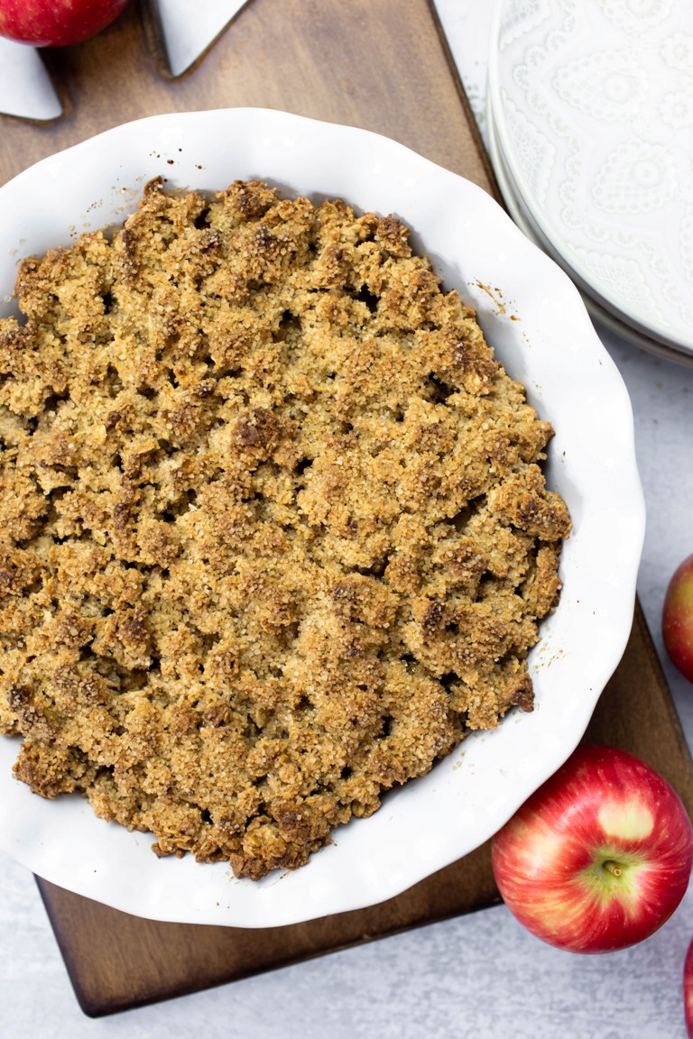 apple crisp in white pie dish with red apples