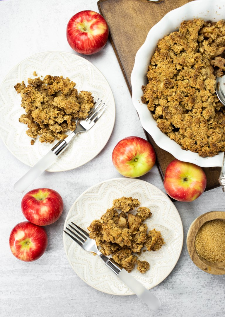 overhead of 2 plates of vegan apple crisp with red apples