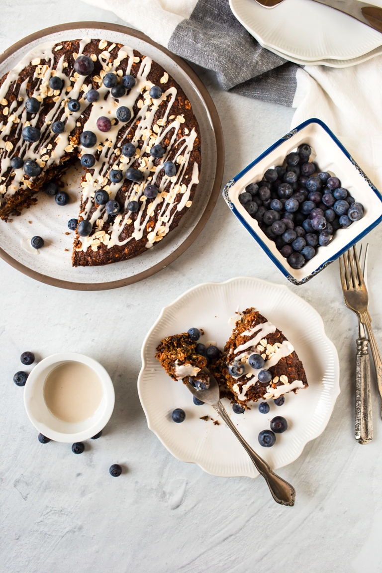 slice of vegan berry breakfast cake on plate with fresh blueberries