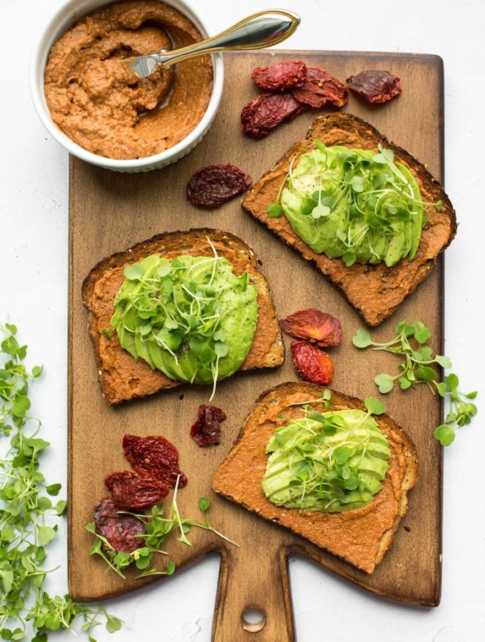 3 slices of avocado toast with bowl of sundried tomato spread