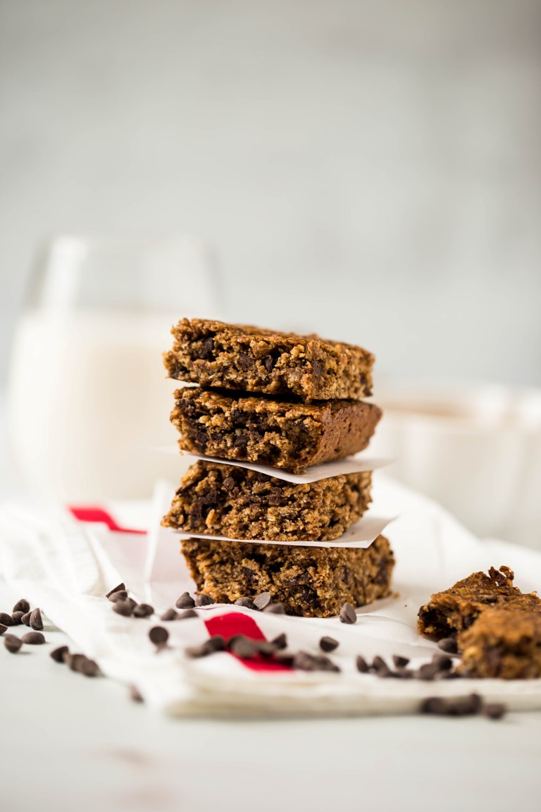 stack of vegan gluten free chocolate chip granola bars with glass of milk