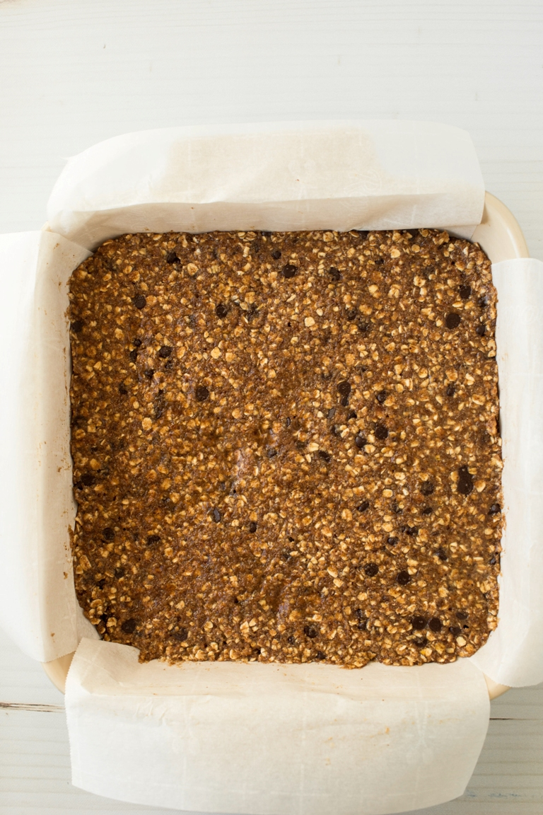 pressed granola bar batter in lined square baking dish
