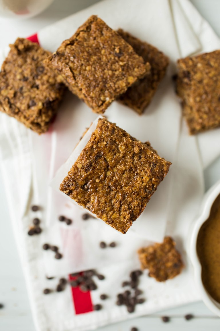 granola bars with chocolate chips on napkin next to almond butter