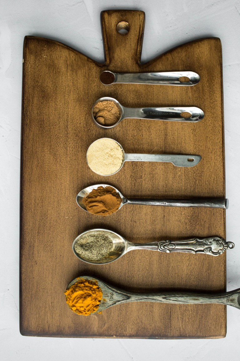 golden milk spices all on separate spoons on wood board