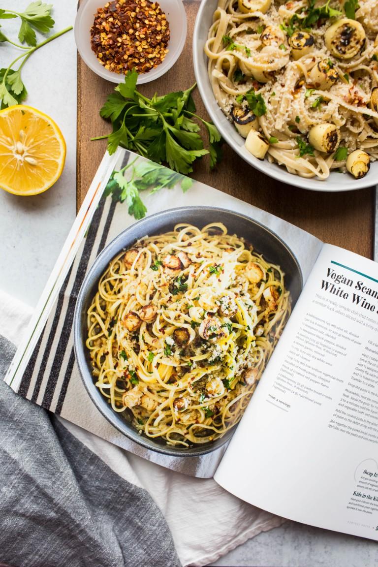 The meatless monday cookbook next to bowl of vegan scampi pasta