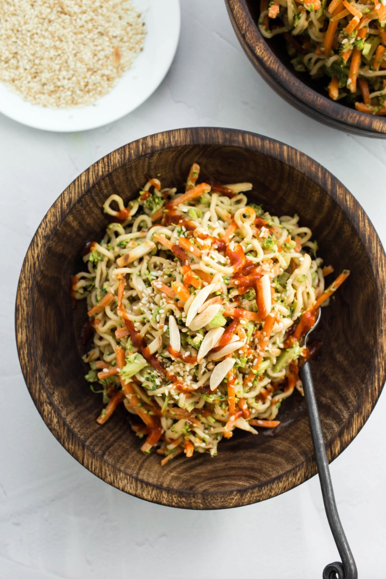 2 wooden bowls of noodle salad with plate of sesame seeds