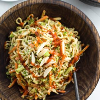 wooden bowl with asian ramen noodle salad with hot sauce drizzle