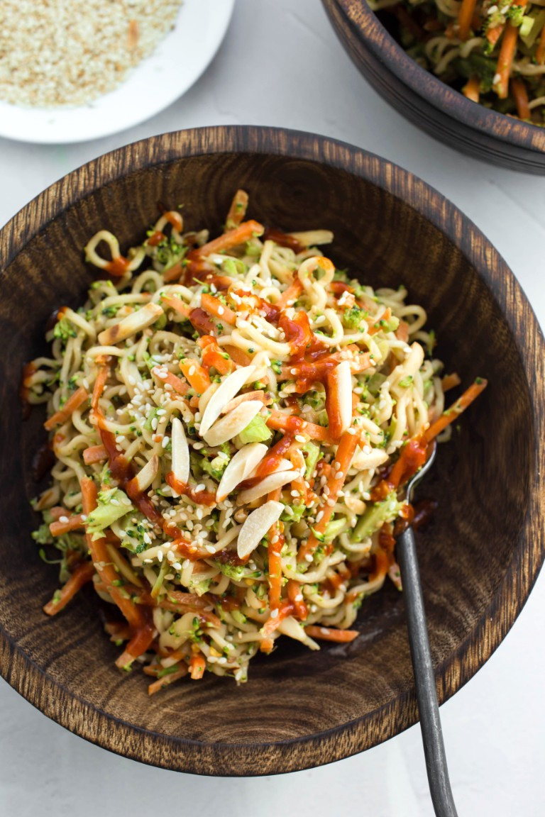 wooden bowl of Asian ramen noodle salad with hot sauce drizzle