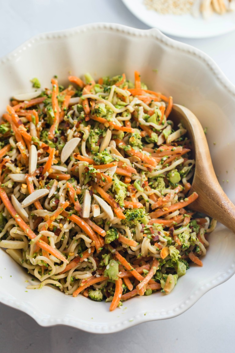 large white bowl of mixed noodles broccoli carrots and tahini asian sauce