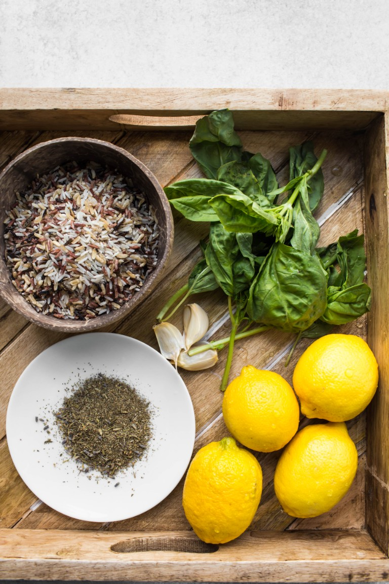 fresh lemons basil leaves wild rice italian seasoning in wood tray