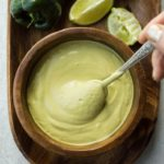 swirling poblano sauce in wooden bowl with spoon