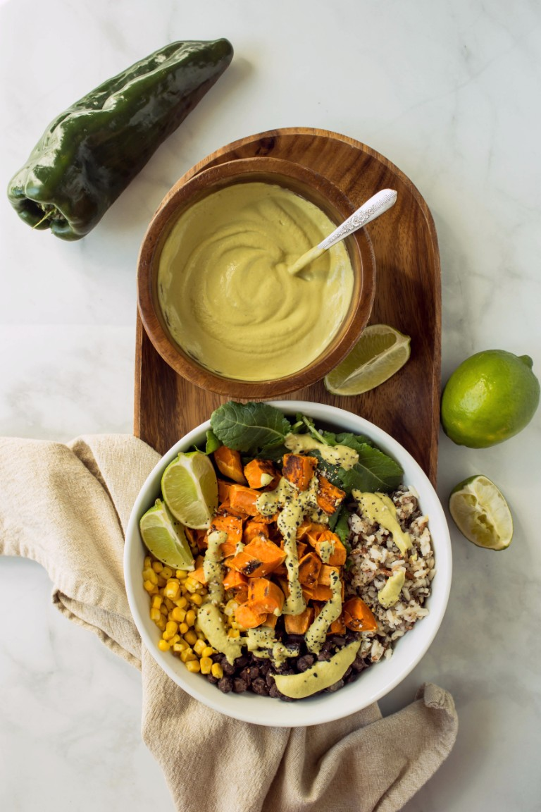vegan bowl with sweet potatoes rice, corn black beans and poblano sauce