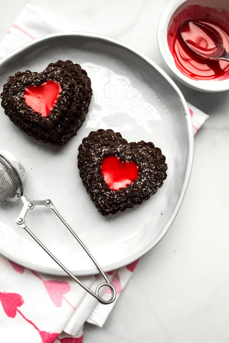 overhead shot of 2 heart chocolate cupcakes with red filling and powdered sugar