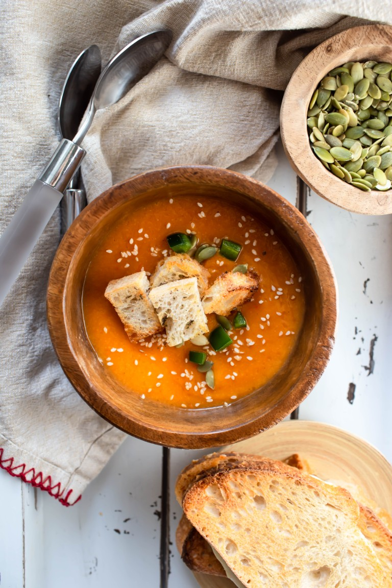wood bowl with soup and croutons and fresh jalapeno