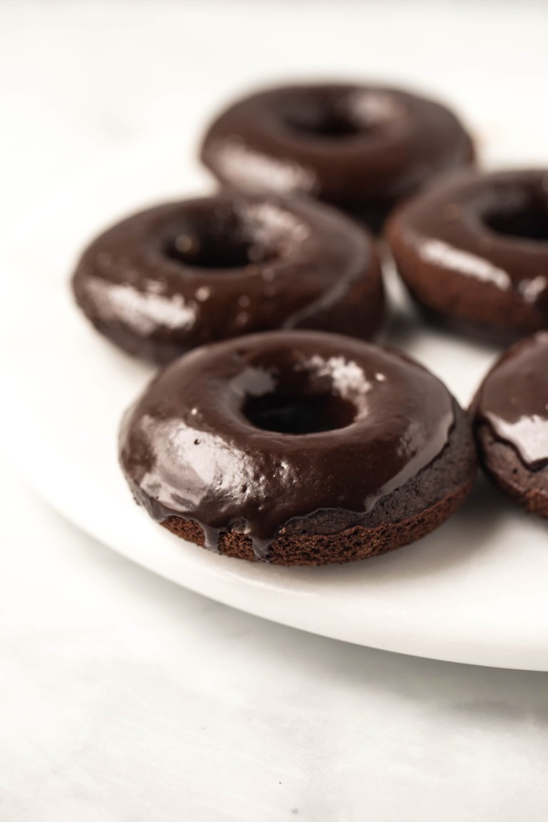 several vegan chocolate donuts on white marble
