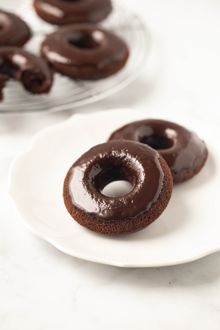 2 chocolate glazed donuts on white plate