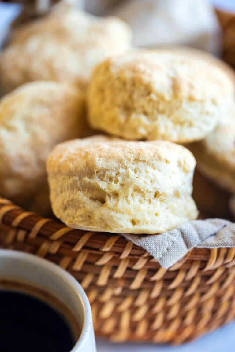 several biscuits in wicker basket with cup of coffee