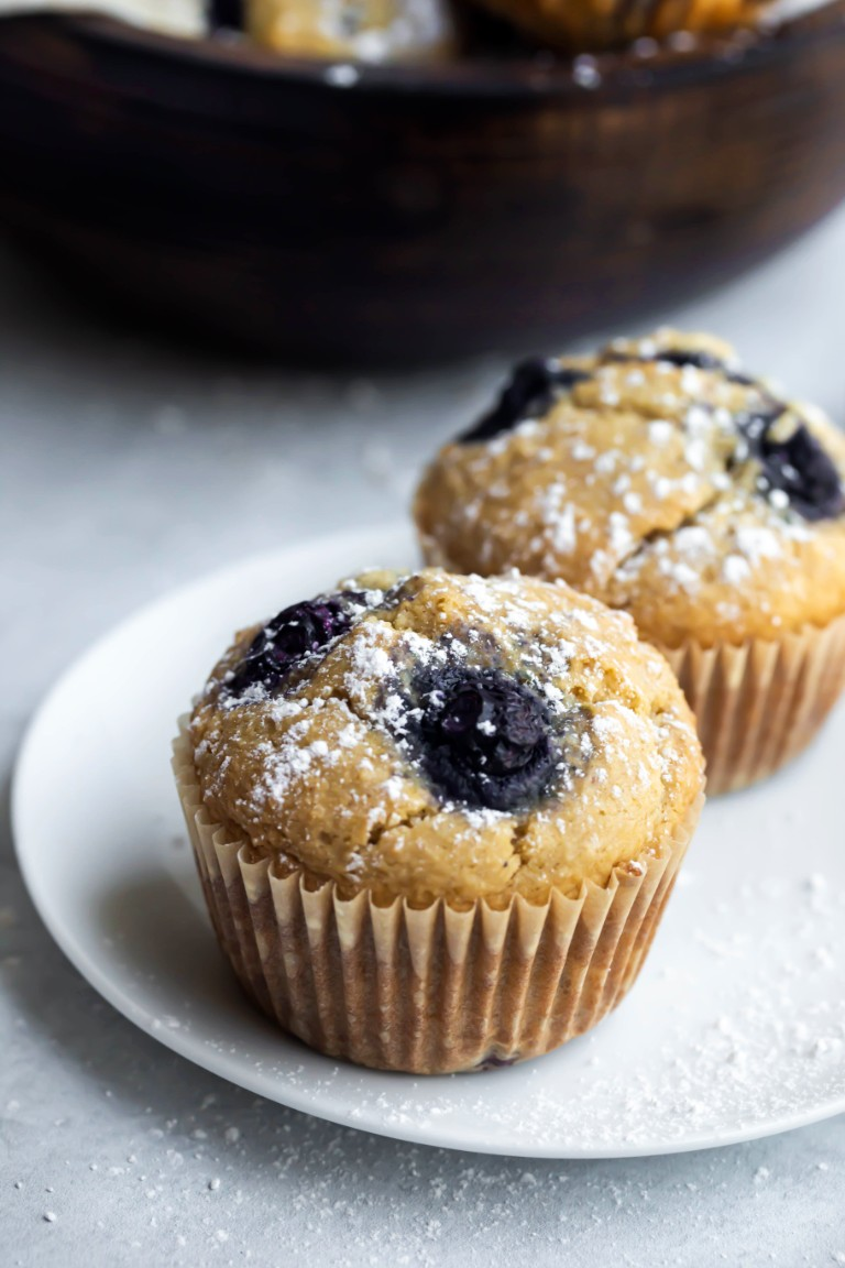 2 muffins on white plate with powdered sugar sprinkled on top