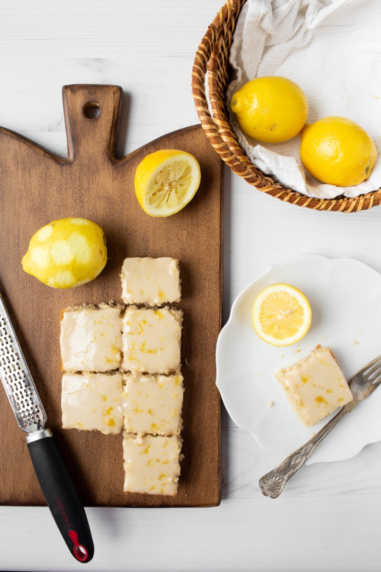 overhead view of several slices of lemon cake with lemons and basket