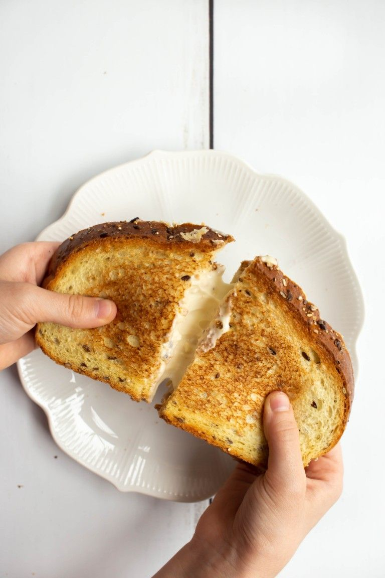 hands holding grilled cheese pulling it apart