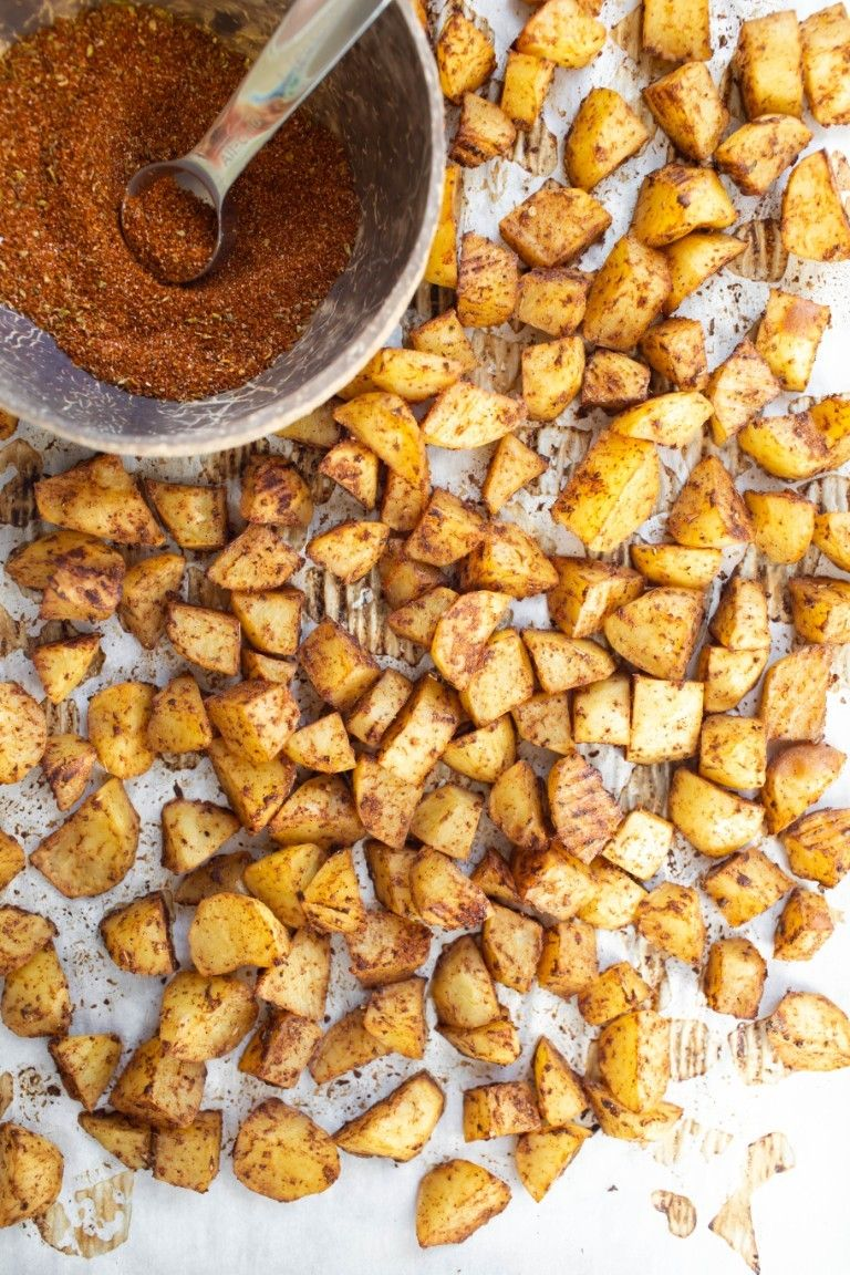 bowl of taco spices next to pan of roasted potatoes