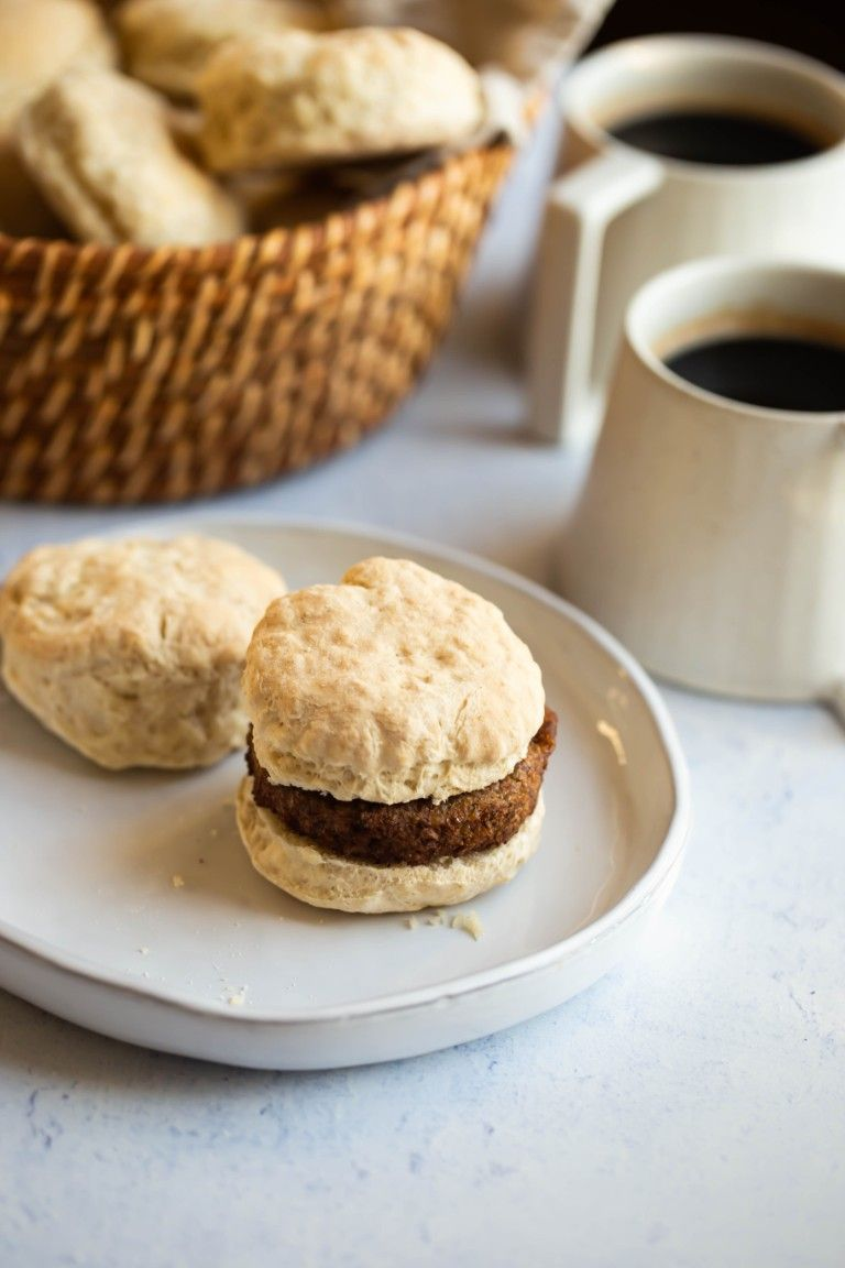 biscuits with vegan sausage on white plate and coffee