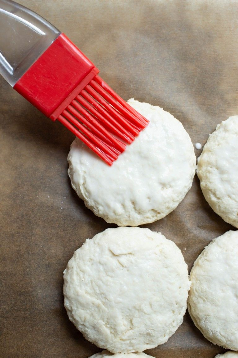 red brush brushing coconut milk on tops of biscuits before baking
