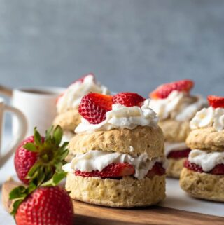 stacked shortcake with whipped cream and strawberries layers on biscuits