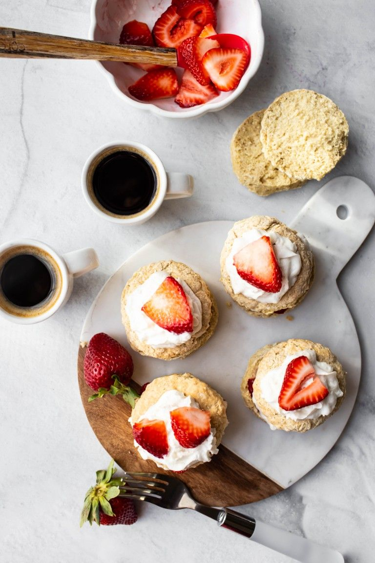 overhead image of shortcakes with whipped cream and strawberries and coffee
