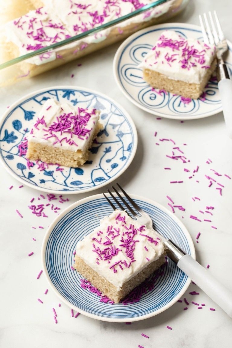 slices of vegan vanilla cake on blue plates with forks