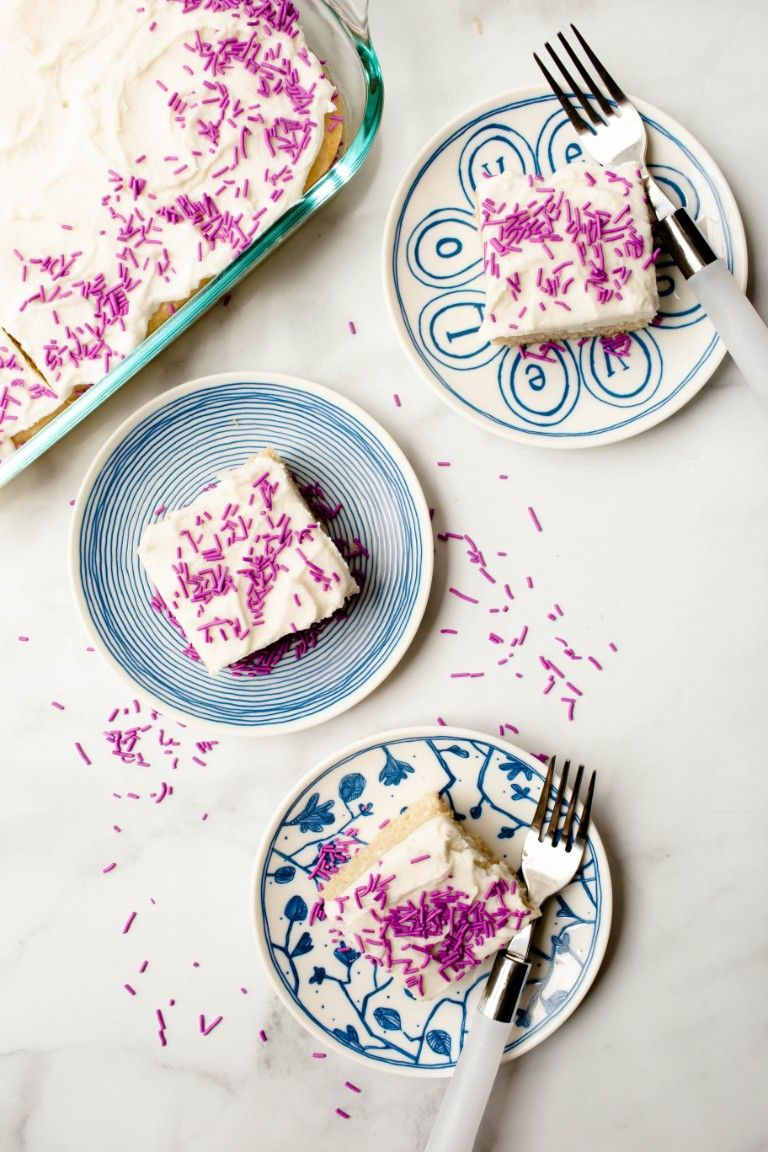 overhead view of 3 blue plates of vanilla cake slices and frosting and purple sprinkles