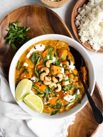 overhead view of white bowl of sweet potato curry with limes and cashews