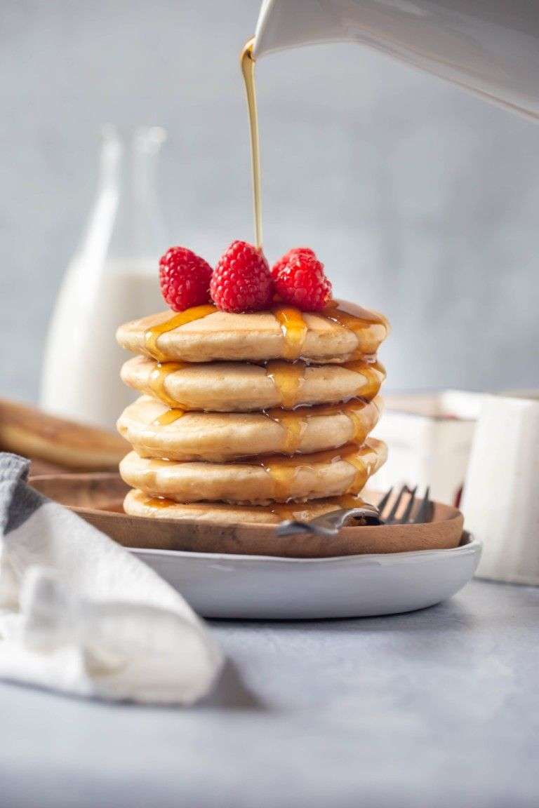 stack of vegan pancakes on round wood plate with raspberries on top