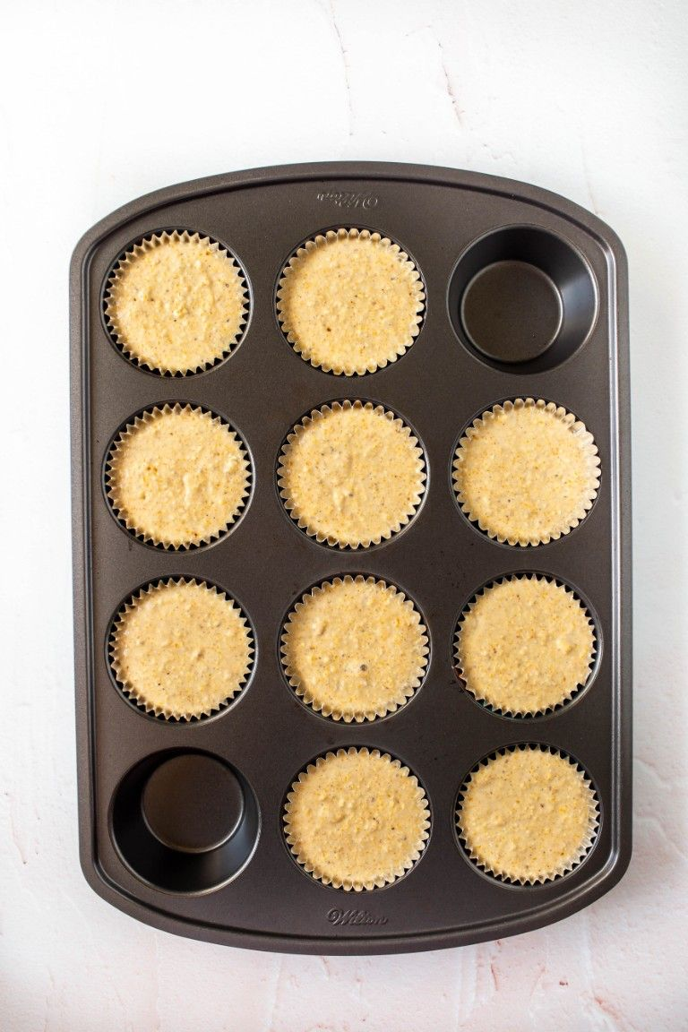 vegan cornbread muffin batter in muffin pan liners before baking