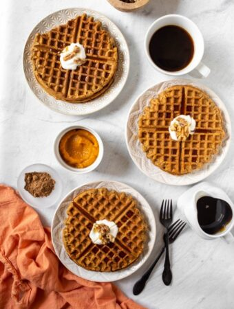 overhead view of 3 plates of pumpkin waffles with syrup and coffee
