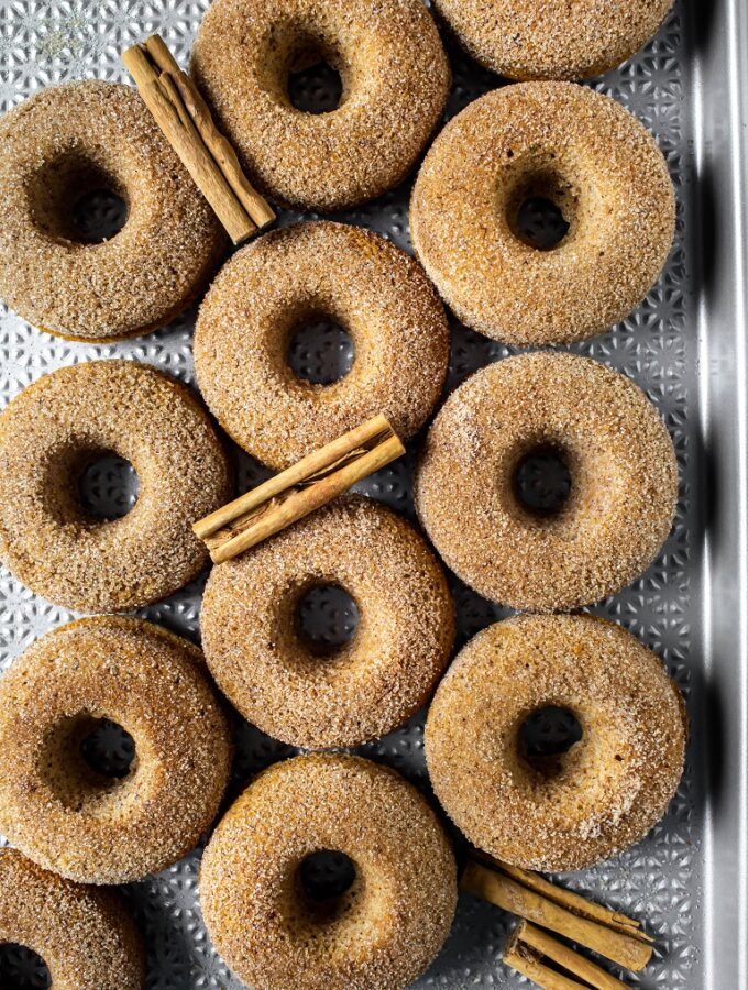 overhead view of several baked vegan apple cider donuts with cinnamon sticks