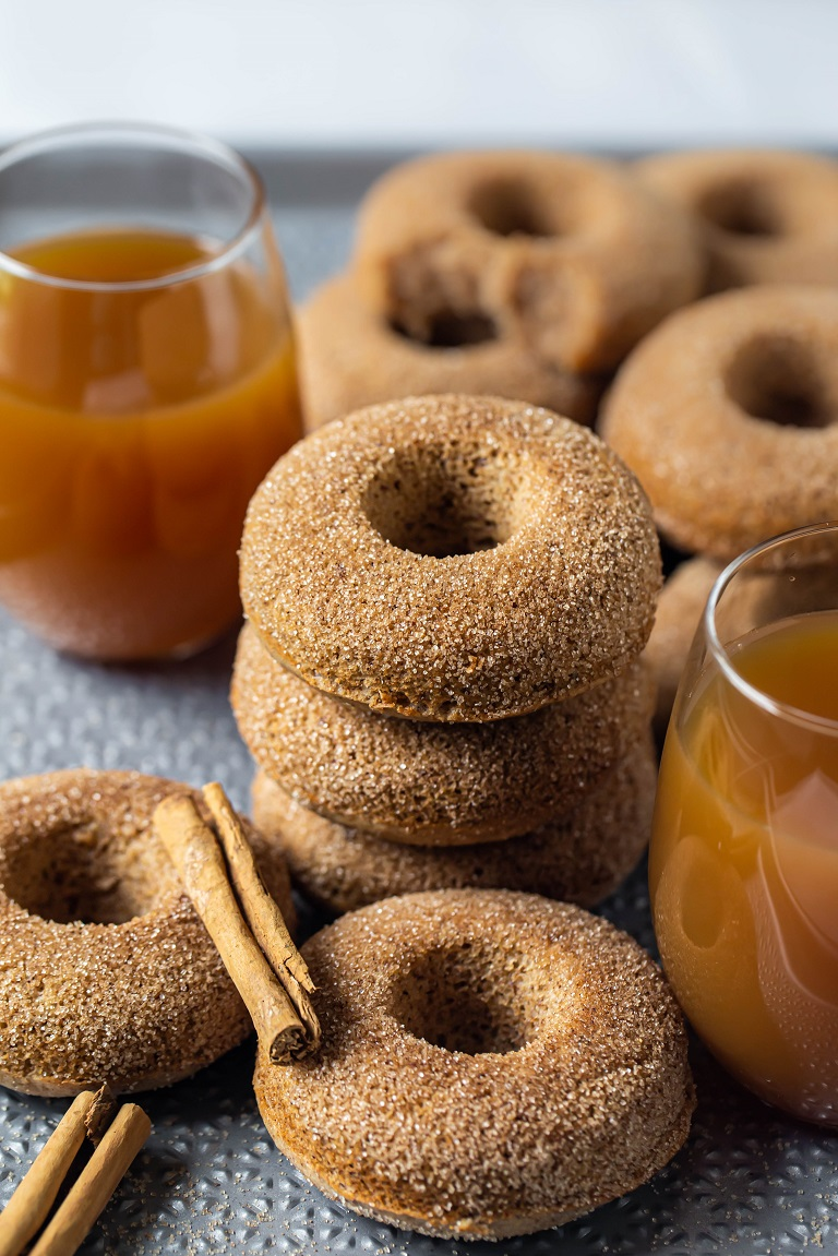 several donuts in between 2 glasses of apple cider