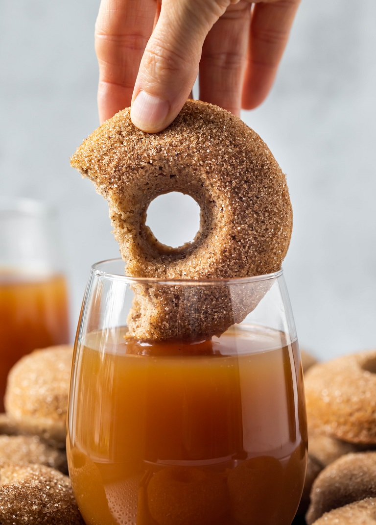 hand dipping donut in glass of apple cider