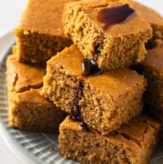stack of beautiful golden vegan pumpkin cornbread on blue round plate
