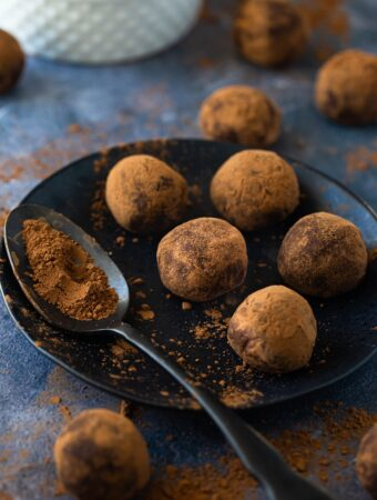 closeup of chocolate truffles on black plate with spoon of cocoa powder