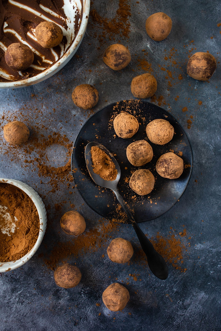 several vegan chocolate truffles on round black plate with spoon