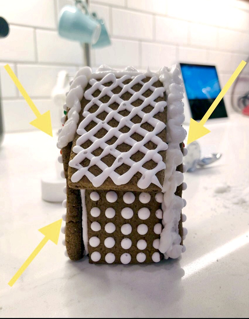 mini gingerbread house with arrows pointing how to pipe frosting on