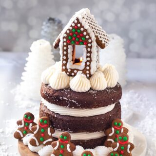 full 3 layer vegan gingerbread cake with frosting and gingerbread house on top
