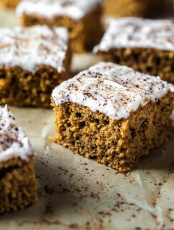 closeup of slice of pumpkin cake with frosting and fresh nutmeg and cinnamon